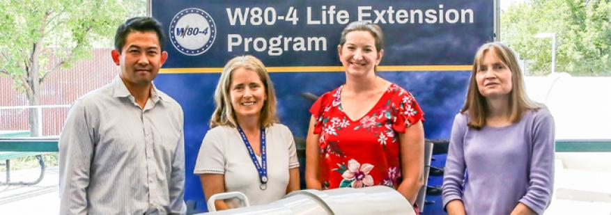 Four people standing in front of a sign with the words W80-4 Life Extension Program.